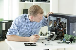Image of man fixing computer at home